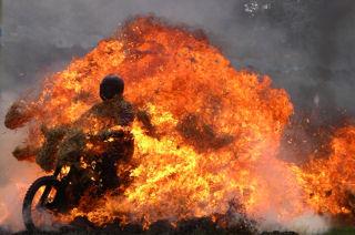 Een stuntrijder rijdt met zijn motor door de vlammen.